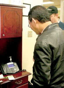 A member of the Philippines contingent listens to a phone conducting part of an e-transaction. Staff Photo by Joe Cowart