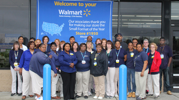 A small representation of the 190 Ahoskie Wal Mart associates gather in front of a banner proclaiming the local business as the nation's Small Market Store of the Year. Staff Photo by Cal Bryant