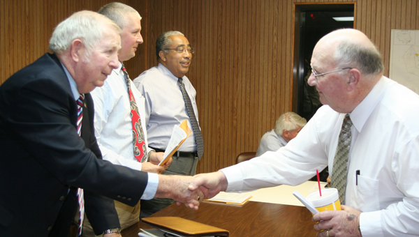 J. Wallace Perry (left), Chairman of the Bertie County Board of Commissioners, greets Powellsville Mayor Thomas Asbell as last week's board meeting. Also shown in the background are, from left, Commissioners Rick Harrell and Ron Wesson. Staff Photo by Amanda VanDerBroek