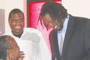 Former Bertie High star Travis Bond (right) signs autographs and shares a laugh at Greater Wynns Grove Baptist Church in Colerain on Sunday. Bond was tabbed in the 7th round of the 2013 NFL Draft by the Minnesota Vikings. Staff Photo by Gene Motley