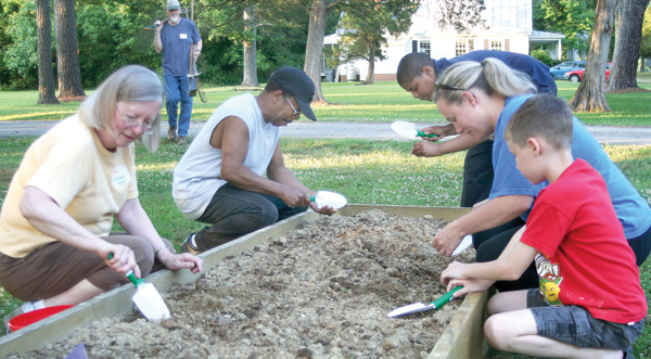 Kneeling from left, Barbara Gosney, Sam Golson, J'Khari Jones, Meredyth Corey and Aidan Corey work the soil in the Woodland Children's Community Garden. Staff Photo by Amanda VanDerBroek