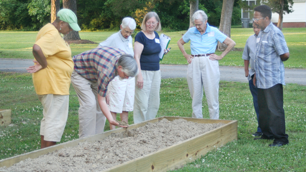 Bob Gosney checks the soil in one of the garden beds planned for Woodland youth. Looking on are, from left, Carita Hall-Reynolds, Anne Outland, Barbara Gosney, Autrey Jenkins, J'Khari Jones and Sam Golson. Staff Photo by Amanda VanDerBroek