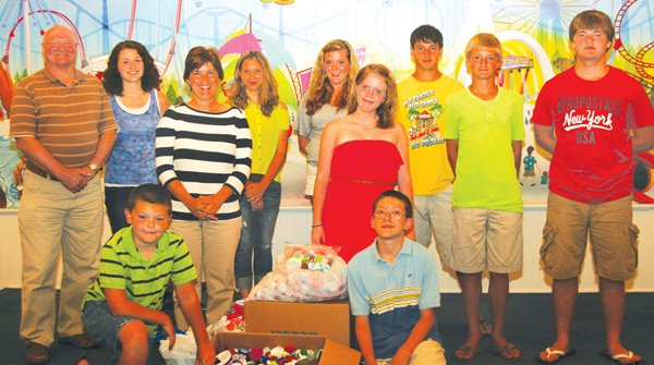 Members of the Powellsville Baptist Church and Mars Hill Baptist Church Vacation Bible School, who collected nearly 25,000 plastic bottle caps, pose at the church with their collection: (front row) Trent Hoggard, Wesley Bandy, (2nd row) Rhonda Barber, Lindsey Faella, (back row) Jim Hopkins, pastor, Tina Brown, Mallory Ward, Hannah Worrells, Paul Northcott, Dylan Harrell, and Nolan Clark. Staff Photo by Gene Motley