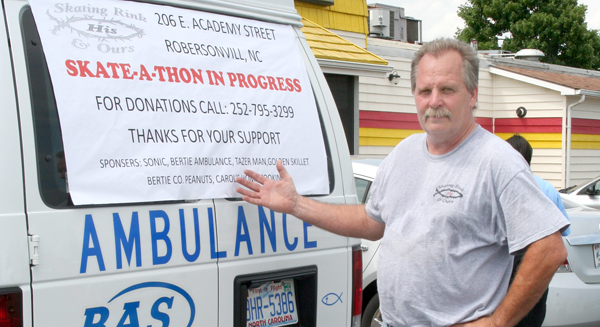 Norman Stocks points to a list of area businesses that sponsored his two-day charity roller skate from Greenville to Ahoskie including Bertie Ambulance Service. Stocks is seeking to raise $20,000. Staff Photo by Gene Motley