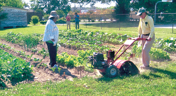Clif Collins (right) is shown tilling the soil as a trainee of the Garden Ministry at Murfreesboro Baptist Church looks on. The Ministry is expanding its offerings following a successful 2013 growing season. Contributed Photo