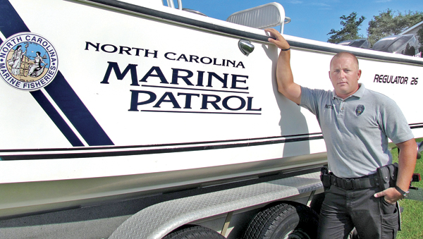 Marine Patrol Officer Chris Lee is shown here with the 26-foot Regulator patrol boat that piqued his interest years ago. Lee, a Colerain native, was recently named as the 2012 Marine Fisheries Enforcement Officer of the Year. Photo courtesy of Division of Marine Fisheries