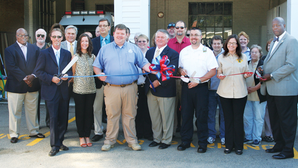 First Med EMS services cuts the ribbon at their new location in Aulander on Tuesday morning, their first day of operation of emergency medical response in Bertie County. Among the dignitaries pictured are (front row, from left) First Med Executive Vice-President Jerry Lecato, First Med Vice-President of business development Sabrena Collins, County Emergency Services Director Mitch Cooper, Aulander Mayor Larry Drew, Bertie First Med Director of Operations Matt Leicester, County Director of Communications Jennifer Stalls, and Bertie County Sheriff John Holley. Staff Photo by Gene Motley