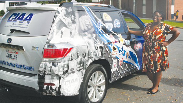 Chowan University Director of Student Life Leah Lambson poses beside the CIAA-Mobile on campus last week. The vehicle is adorned with the logos of all 12 CIAA schools. Staff Photo by Gene Motley
