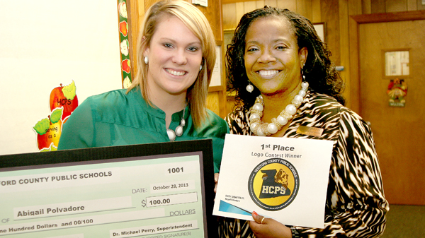 Abigail Polvadore (left), winner of the Hertford County Public Schools logo contest, poses with her $100 prize winner's check alongside HCPS Public Information Officer Brunet Parker. Polvadore's logo beat out 35 other entries. Staff Photo by Gene Motley