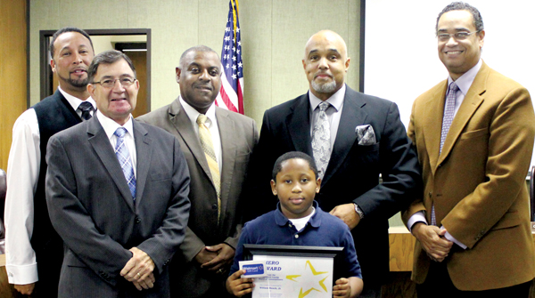 "William Bunch, a 3rd grade student at Bearfield Primary School, poses with Hertford County Commissioners (from left) Howard Hunter III, Johnny Ray Farmer, Ronald Gatling, Curtis Freeman, and Chairman William Mitchell at the Commissioner's meeting on Monday. Bunch is credited with saving his family from a house fire at their home on Newsome Grove Road in Ahoskie on the morning of Nov. 1. In addition to the ""Hero Award"", William also received a $20 Wal-Mart gift card. Contributed Photo"