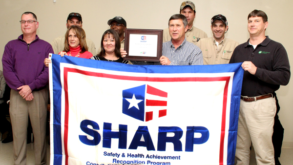 Displaying the SHARP Flag and certificate are, front row from left, Eric Smith (OSHA Safety Consultant) and Roanoke Electric Cooperative Safety Team members Sherwynn Best, Rebecca Alston, Billy Joe Yates and David Lane; along with back row from left, Allen Enrico, Tim Bowser, Charles Bryant, and Clifton Neatherly. Staff Photo by Cal Bryant