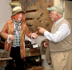 The Mad Hatter (aka Dennis Helsel) interacts with a guest as he shares the history of tinsmith Richard Evans during Thursday's portion of the Candlelight Christmas Tour. Staff Photo by Cal Bryant