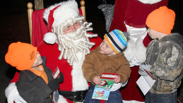 "Santa is the center of attention among these three brothers as each shared their Christmas ""wish lists"" with Jolly Old St. Nick during his visit to the Ahoskie Tree Lighting Ceremony held Saturday night. Staff Photo by Cal Bryant"