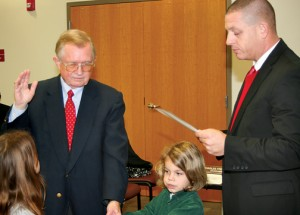 Newly-elected Ahoskie Town Councilman Charles Freeman is sworn in by Mayor G. Brien Lassiter at Tuesday's Council meeting. Freeman, who represents Ahoskie Ward-A, is flanked by his grandchildren, Aurora (right) and Cyrus (left) Freeman holding the Bible. Staff Photo by Gene Motley