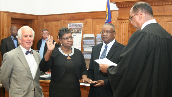 Vasti James is sworn in by Superior Court Judge Cy Grant (right) as the new Bertie County Clerk of Court following the retirement of long-time Clerk John Tyler (left). Tyrone James is also shown as he holds the Bible for his wife's oath. Staff Photo by Gene Motley