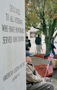 Military veteran Paul Williams sits adjacent to the American Legion's Veterans monument, awaiting the start of Tuesday's ceremony. Staff Photo by Gene Motley