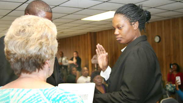 """Altessie """"Tess"""" Taylor receives the oath of office as the new Chief of Police in Rich Square from Town Clerk Frances Futrell on Friday. Her husband, Max (faces partially hidden), holds the Bible. Staff Photo by Gene Motley"""