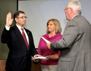 With his wife, Paula, holding the Bible, Commissioner Johnnie Ray Farmer (right) accepts the oath of office from Murfreesboro Mayor John Hinton. Staff Photo by Cal Bryant