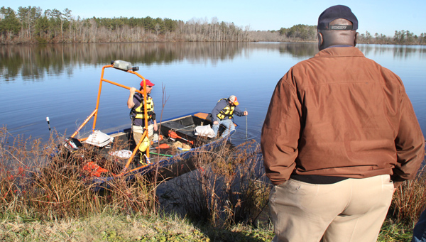 Northampton County Sheriff Jack Smith watches from the road bank as Conway-Severn Rescue Squad members probe the waters of Doolittle's Millpond on Saturday as they search for Donald Eugene Williams. Staff Photo by Cal Bryant