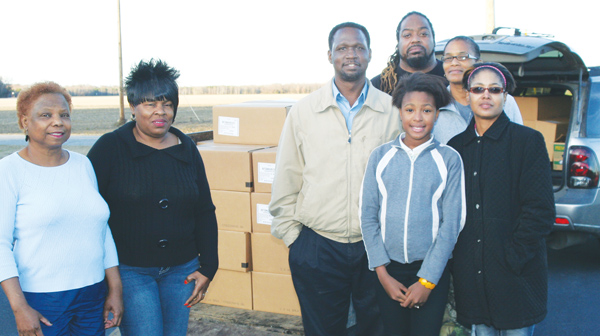 With stacks of food boxes in the background, Ishmael Muldrow (tan jacket) prepares to load up for distribution across Bertie County. Pictured are (from left, front): Flo Brockington; Brenda Gilliam; Muldrow; his wife, Sharon; and daughter, Shaniah; and (back row) David Hayes and Josephine Jenkins. Staff Photo by Gene Motley