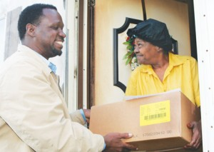 Fannie Louise Cobb of Merry Hill accepts one of the food distribution packages from Ishmael Muldrow during a stop for one of his Bertie County giveaways. Staff Photo by Gene Motley