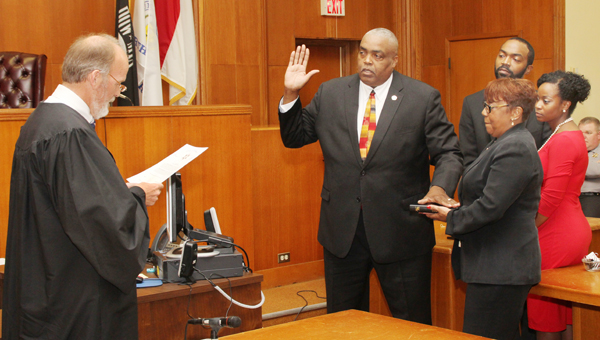 For the fifth time in his career, Juan Vaughan (center) accepts the oath as Sheriff of Hertford County as his wife, Gail, holds the Bible while his son, Andre, and his girlfriend, Austin Hill, witness the occasion. The oath was administered Monday morning by Judge Thomas Jones Jr. (left). Staff Photo by Cal Bryant