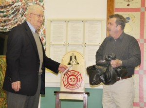 Buck Carter rings the bell of a gift given in honor of his 57 years to the PVFD. At right is PVFD member David Harrell. Staff Photo by Cal Bryant