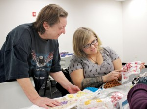 """Johanna Collins (left) and Jen Meyers work to complete one of the many knitting projects performed by the """"Granny Squares of Love."""" Photo by Macaulay Chilaka Jr."""
