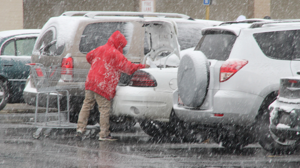A local resident loads groceries into their vehicle in the parking lot of the Ahoskie Piggly Wiggly as snow falls on Tuesday afternoon. Local grocery stores were packed again on Wednesday as area residents were prepping for a larger snowstorm expected to arrive Wednesday night and last well into Thursday morning. Staff Photo by Cal Bryant