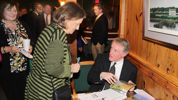 Scott Mason (seated) chats with Beckisue Joyner as he prepares to autograph a copy of his latest book. Mason served as the keynote speaker at Monday night's Murfreesboro Chamber of Commerce Banquet. Staff Photo by Cal Bryant
