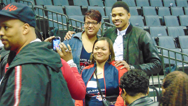 """Bertie High School grad and current Atlanta Hawks player Kent Bazemore (right) poses for a photo with two of his Bertie fans – Takiyah Leary (left) and Tamera Lee (foreground) – after they joined others on a bus trip to Charlotte to see Bazemore play. Photo by J.W. """"Russ"""" Russell"""