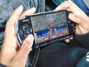 """While en route to Charlotte, Raheem Mitchell of Windsor occupies his time by playing a video game featuring his favorite NBA team – the Atlanta Hawks. Photo by J.W. """"Russ"""" Russell"""
