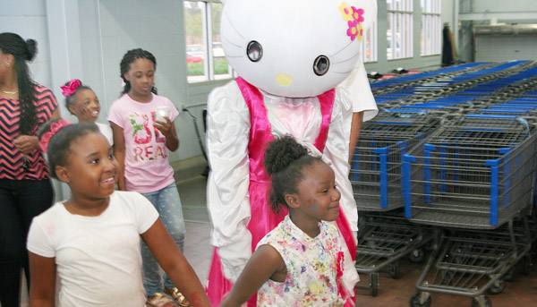 """Azariah Goddard (flowered blouse) and her cousin, Kayla Sessoms (left) accompany """"Hello Kitty"""" inside the Ahoskie Wal-Mart for a shopping spree on Saturday. Staff Photo by Gene Motley"""