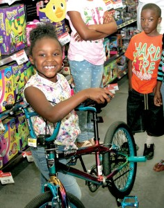 Azariah Goddard is all smiles as she poses with one of her donated birthday presents, a brand-new bicycle. Staff Photo by Gene Motley