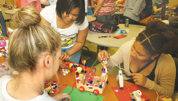 Hertford County Early College students work on projects at the Maker Faire, a day of arts and crafts from the traditional to the high tech. Students (from left) Shelby Cooke (back to camera), Akiya Russell, and Shakira Gay work on their designs. Contributed Photo by Addison Hoggard