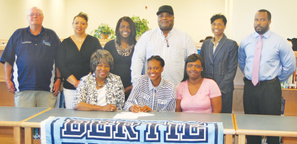 Former Bertie High basketball player De'Najah Porter (seated, center) signs her National Letter-of-Intent to attend Fayetteville State University in the fall.  Joining the ex-Falcon forward are (seated, from left): BHS girls basketball coach Alice Lyons; Porter; Keyarta Ryan, mother; (standing, from left) BHS athletic director Randy Whitaker; Carshenia Ryan, grandmother; Akia Jordan, sister; Jerry Ryan, grandfather; Daphne Williams, Bertie STEM Principal; BHS Principal Rickey Eley. Staff Photo by Gene Motley