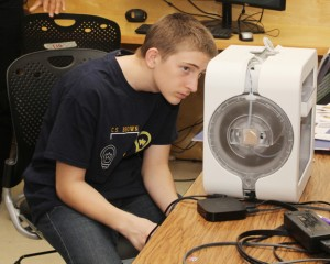 STEM student Brandon Jager watches closely as a device scans a 3D image of a project he designed. Staff Photo by Cal Bryant