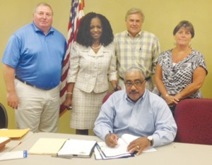 """Bertie County Board of Commissioners chairman Ronald D. """"Ron"""" Wesson (seated) signs the new contract between the county and Republic Services on the operation of the county's recycling and solid waste convenience centers.  Pictured are fellow Commissioners (from left): Stewart White, Ernestine """"Byrd"""" Bazemore, John Trent, and Vice-chairman Tammy Lee. Contributed Photo"""