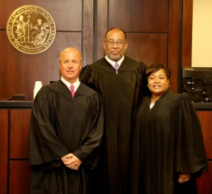 Superior Court Judge Cy Grant (center) poses with retired District Court Judge Thomas Newbern and current Chief District Court Judge Brenda Branch during a courtroom recess on Tuesday morning. Staff Photo by Cal Bryant