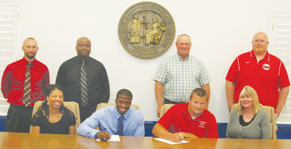 Former Gates County High football players Andrew Wiggins and Nick Herman sign their National Letters-of-Intent Thursday at the Gates County Board of Education.  Pictured are: (seated, from left) Leslie Wiggins, Andrew's mother; Andrew Wiggins; Nick Herman; Rae Herman, Nick's mother; (standing, from left) Jonathan Hayes, Assistant Principal, GCHS; Rodney Wiggins, Andrew's father; Mark Herman, Nick's father; and Matt Biggy, Gates County High School football coach. Staff Photo by Gene Motley
