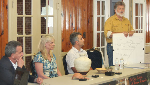 Brent Lane (right) and a group of First Colony Foundation archeologists address a large audience at the Windsor Community on the theory the Lost Colony relocated to Bertie County in 1587.  In the foreground are artifacts excavated near Merry Hill. Staff Photo by Gene Motley