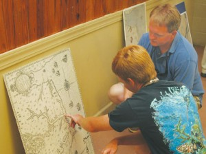 Jordan Rose (left) of Windsor points to an area indicated now as Bertie County on one of the 16th century maps used by New World explorers as Jody Sary of Merry Hill looks on.  Staff Photo by Gene Motley