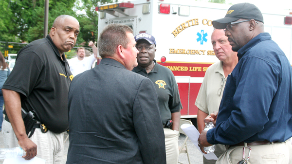 """Area law enforcement officials brief each other during """"Operation Take as Directed"""" Tuesday morning in Windsor. From left are Hertford Co. Sheriff Juan Vaughan; SBI Agent Donnie Varnell (back to camera); Northampton Co. Sheriff Jack Smith; Murfreesboro Police Chief Darrell Rowe; and Bertie Co. Sheriff John Holley. Staff Photo by Gene Motley"""