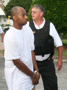 Bertie County Sheriff's Sergeant Ed Pittman escorts a suspect for processing. Twenty of 28 persons had been arrested as of midday Tuesday accused of trafficking in illegal narcotics. Staff Photo by Gene Motley