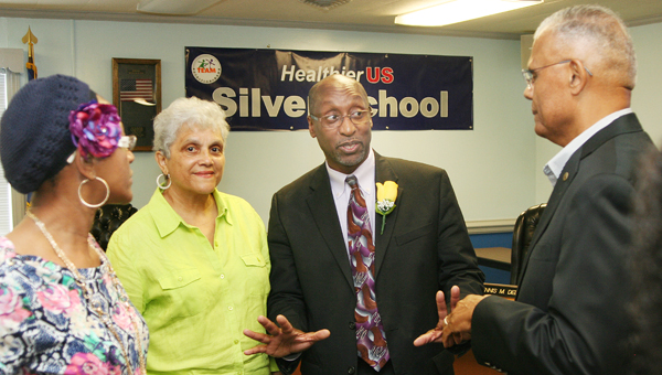 Hertford County Public Schools superintendent Dr. Michael D. Perry (second from right) speaks with well-wishers, to include Dr. Claude Odom (right) at a farewell reception given in his honor Thursday.  After three years with HCPS, Perry has taken a similar position in northern Virginia. Staff Photo by Gene Motley