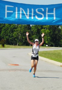 """Jenny Wilson of Winterville crosses the finish line in a time of 1 hour-27-minutes-42 seconds to take top women's honors. Photo by JW """"Russ"""" Russell"""