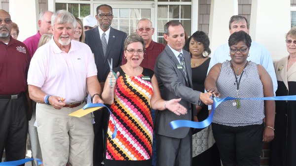 Foreground from left: Gatesville Mayor and Gates County Chamber of Commerce President Elton Winslow joins with Meridian Senior Living officials Debra Warren and Sean McAuliffe are joined by a host of well-wishers as they cut the ribbon to formally open Gates Health & Assisted Living. Staff Photo by Cal Bryant
