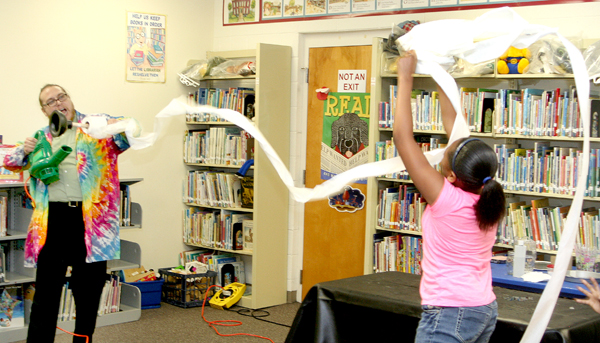 Ternica Mitchell (right) assists Joshua Daniels with another science experiment at the Hertford County Library. Scienetellers say they want the kids have fun when they participate in the lessons. Staff Photo by Gene Motley