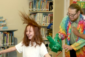 Scienceteller Joshua Daniels (right) demonstrates wind current on volunteer Jameson Brown during a performance at the Winton branch of the Albemarle Regional Library on Thursday.  Sciencetellers – part scientist, part storyteller – use interactive lessons and storytelling to teach science to young kids. Staff Photo by Gene Motley