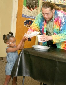 Jaiden Smith assists Joshua Daniels with an experiment on evaporation by pouring acetone onto styrofoam. Both wear protective goggles to prevent an accidental eruption. Staff Photo by Gene Motley